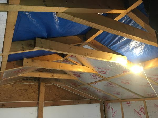 Installation of insulation into the roof apex. The dust falling from the board as they are positioned in place made this an unpleasant job.